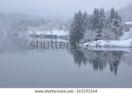 A snowy landscape against the clear icy water of a lake. - stock photo