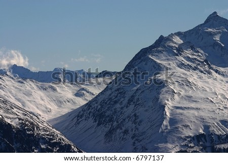 A snowy landscape of mountains in winter against a blue sky.