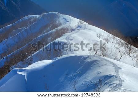 A snowy mountain trail - stock photo