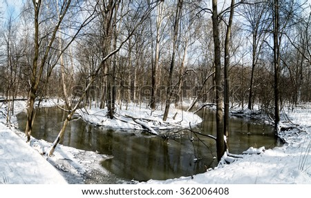 A snowy winter scene along bend in a creek with snow and beautiful blue skies. - stock photo