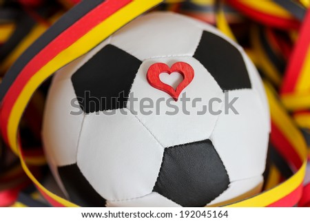 a soccer ball, a heart and streamers in black, red, yellow - stock photo