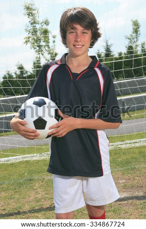 A soccer player on the play field. The boy hold a ball. - stock photo