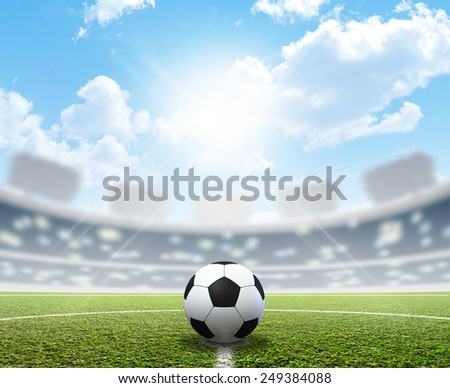 A soccer stadium with a marked green grass pitch and a soccer ball in the center in the daytime under a blue sky - stock photo