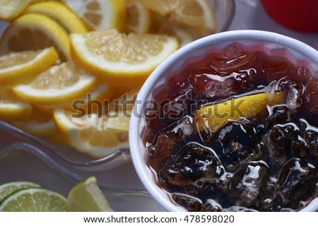 A soda and liquor drink in a plastic cup with ice and lemon. Next to a bowl of lemons. Summertime barbecue party refreshing cocktail.