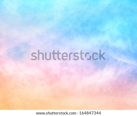 A soft cloud background with a pastel colored orange to blue gradient.  Image features a pleasing paper grain and texture at 100 percent. - stock photo
