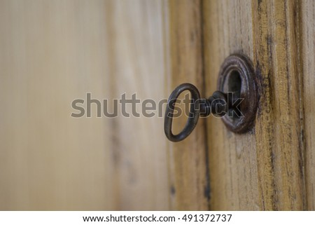 A soft focus image of an old, metal and rustic key inside a lock of a wooden closet.