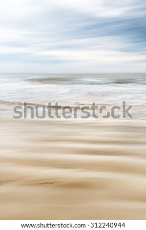 A soft focus seascape with blurred panning motion combined with a long exposure.  Image displays soft, desaturated colors.