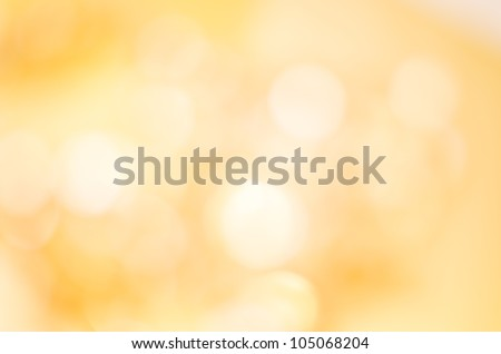 A soft glowing golden yellow bokeh background in landscape (horizontal) orientation. - stock photo