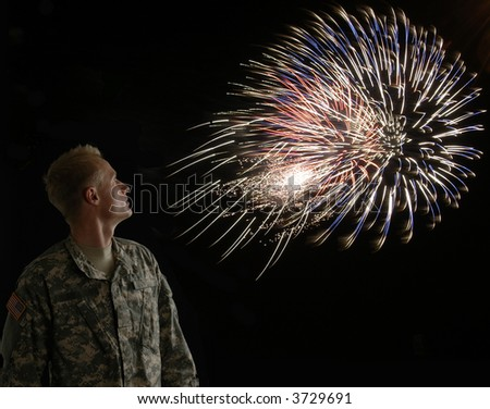 A soldier illuminated by the fireworks over his shoulder - stock photo