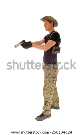 A soldier in camouflage pants, hat and black t-shirt aiming his hand gun isolated on white background.  - stock photo