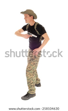 A soldier in camouflage pants, hat and black t-shirt pulling his hand gun out of the holster, isolated on white background.  - stock photo