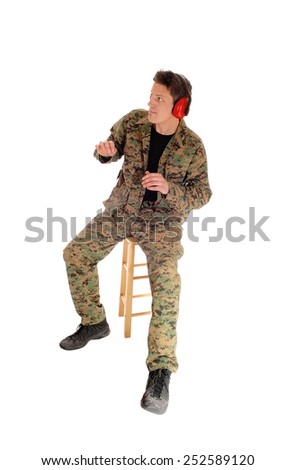 A soldier in camouflage uniform sitting on a chair in a scary position with ear protection, isolated for white background.  - stock photo