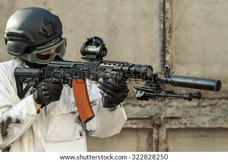 a soldier in the winter camouflage suit aims of the AK-47 - stock photo