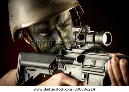 A soldier in war paint looks through the scope of automatic rifles. Military, war. Special forces.