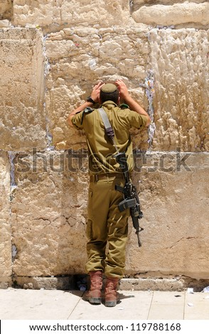 A soldier prays in the Western Wall (kotel) - stock photo