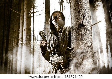 A soldier wearing gas mask is fighting in the forest