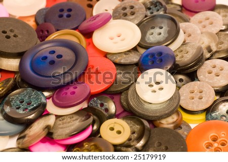 A solid background of a variety of different sizes and colors of buttons