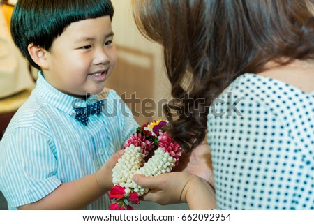 A son gives a Thai garland to his mom.