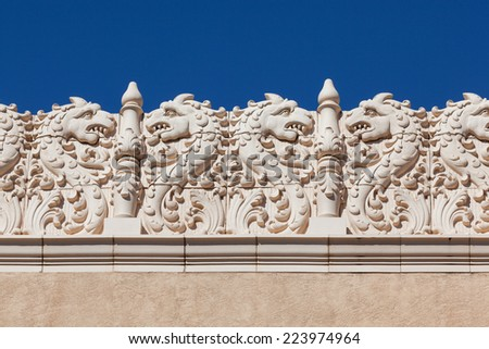 A southwestern building with tiles creating a dragon theme are used as decoration along the top edge. - stock photo