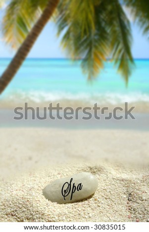 a spa stone in the sand on a tropical beach - stock photo