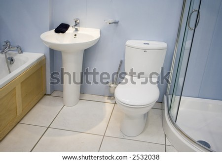 A spacious modern blue bathroom with white suite - stock photo