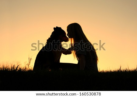 a special and serene moment as a girl is lovingly hugging her German Shepherd Dog, silhouetted against the sunsetting sky - stock photo