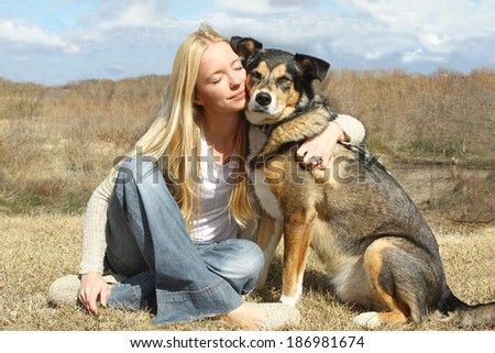 a special and serene moment as a happy woman with her eyes closed is lovingly hugging her large German Shepherd dog outside. - stock photo