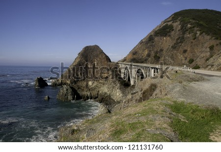 A spectacular view of mountain and ocean and bridge along California's Highway 1. - stock photo