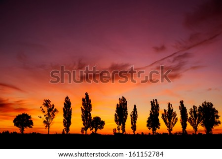 A spectacular, vivid  sky at sunset . Photographed just after the sun dipped below the horizon and after as storm clouds were dissipating. - stock photo