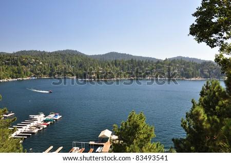 A speed boat cruises around beautiful Lake Arrowhead in the San Bernardino mountains of California. - stock photo