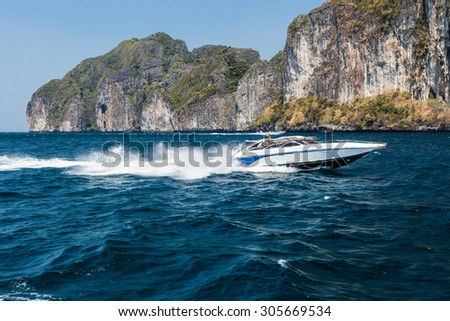 a speed boat passing near a cliff in Phi Phi Island, Thailand - stock photo