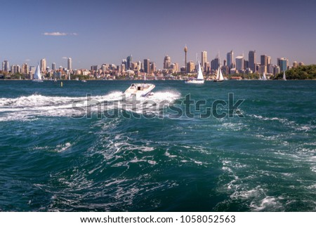 A speedboat heads towards the sky line of downtown Sydney and yatchs sailing within Sydney harbour, Australia