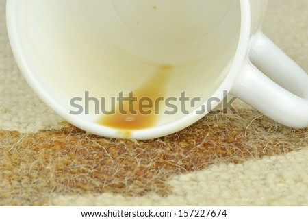 A spilled cup of coffee on a carpet  - stock photo
