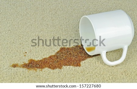 A spilled cup of coffee on a carpet with stain - stock photo