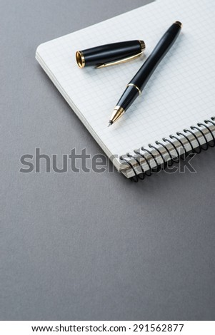 A spiral notebook with black ball pen on the grey table