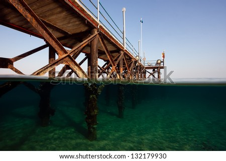 A split shot of a hotel jetty leading into a tropical sea - stock photo
