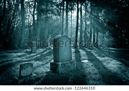 A spooky cemetery with light rays coming through the trees and fog adding to the creepy atmosphere. - stock photo