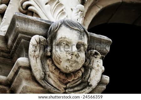 a spooky old statue of child's head amongst wings