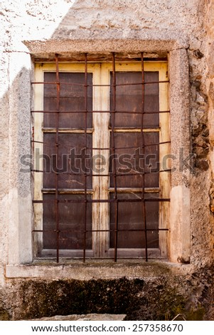 a spooky window of an abandoned house with broken and dirty glass - stock photo