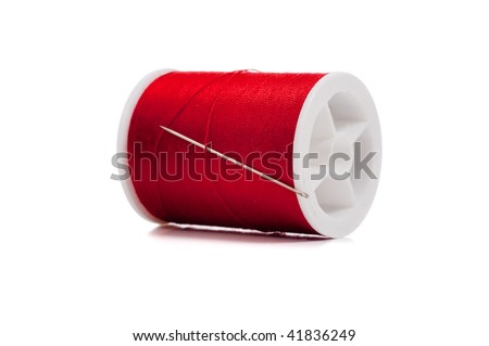 A spool of red thread and a needle on a white background - stock photo