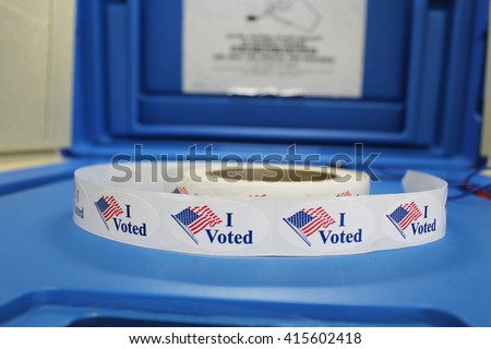 "A spool of Red white and blue ""I voted"" stickers with American flag are on a blue voting booth platform.  - stock photo"