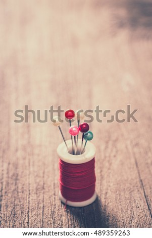 A spool of sewing thread with needles on a wooden background in vintage style color