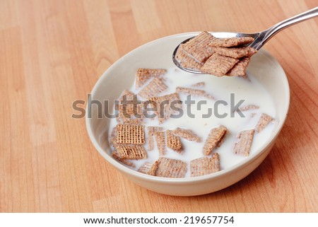 A spoon with malted cereal on it hovers above a bowl of cereal and milk - stock photo