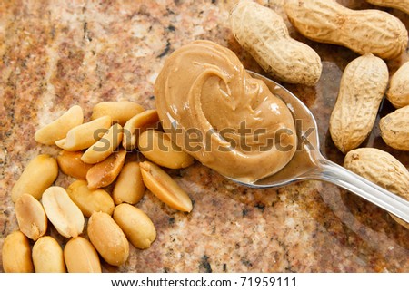 A spoonful of creamy peanut butter is a healthy food and a dangerous allergen - stock photo