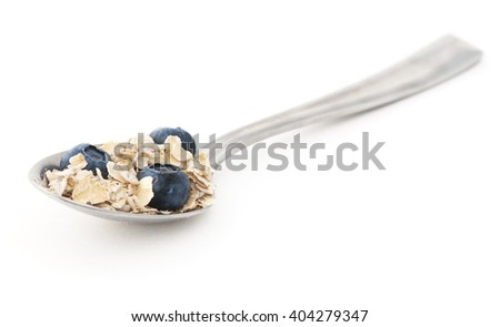A spoonful of oatmeal and blueberries on a white background.