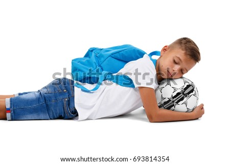 A sportive kid with a soccer ball lying on the ground. A little footballer isolated on a white background.
