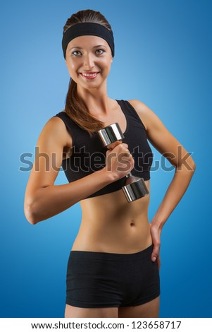 a sports girl posing with dumbbell