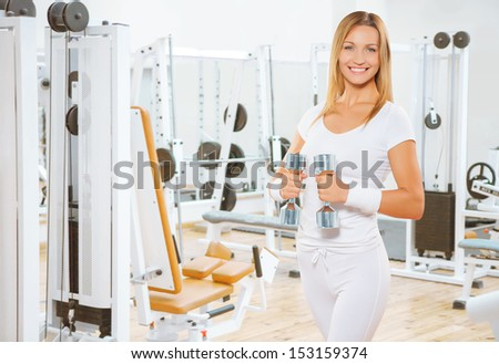 a sports smiling female holding weights - stock photo