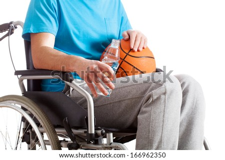 A sportsman with a basketball and water on a wheelchair - stock photo