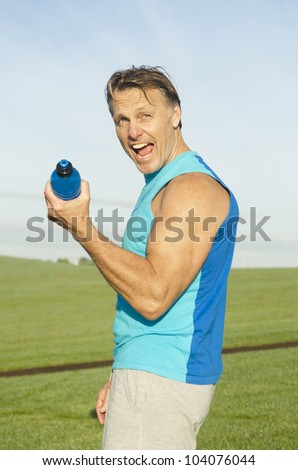 A sporty man flexing his muscles using his water bottle for fun.
